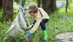 Ung gutt som plukker søppel ute i naturen