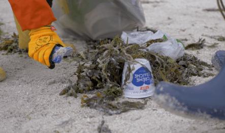 Nærbilde av en hånd som rydder plastsøppel ved Marineholmen i Bergen