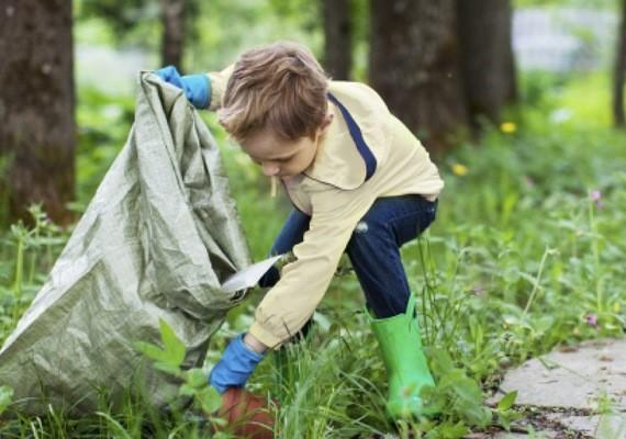 Ung gutt plukker plastsøppel i naturen