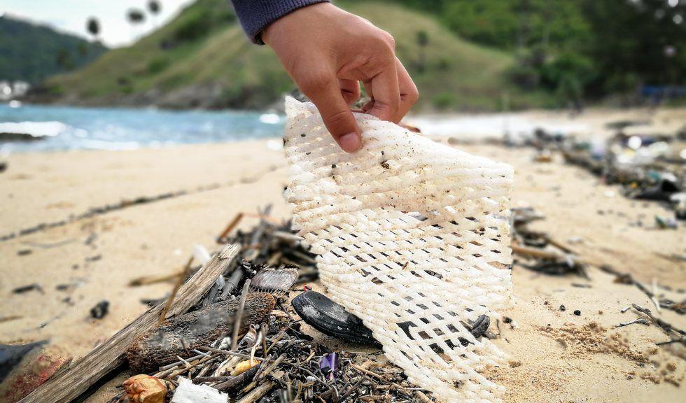 En hånd som rydder plastsøppel fra en strand